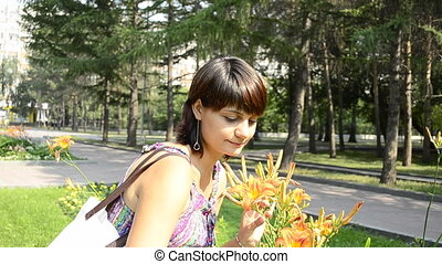 young pregnant woman sniffing flowers