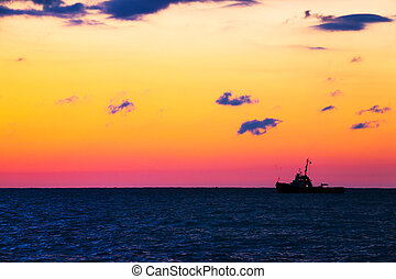 Fishing ship at sea with sunset