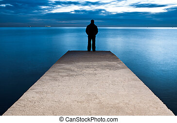 Man is standing on a jetty looking the sunset
