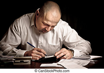Man paying bills - Man concentrating while working on...