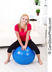 Happy woman in pilates ball