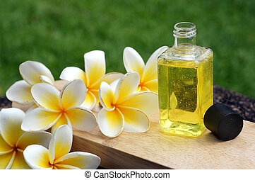 Massage oil for tropical spa concept with plumeria flowers