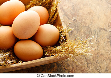 Brown eggs in wooden square bowl