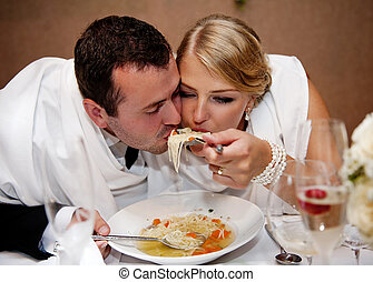 Wedding reception - Bride and groom are eating at the...
