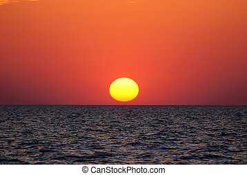 Bright sunset with large yellow sun under sea surface -...