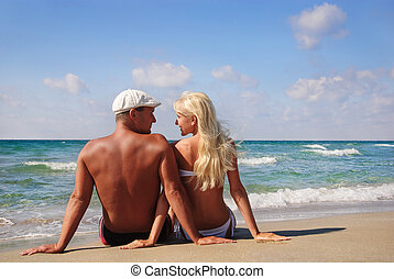 loving couple sitting on the sea sand beach and look at each...