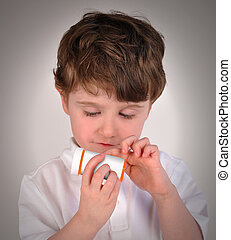 Child Looking at Pill Bottle Prescription - A young boy is...