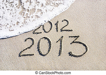 Happy New Year 2013 replace 2012 concept on the sea beach