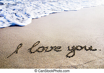 "words ""I love you"" outline on the wet sand with the wave..."