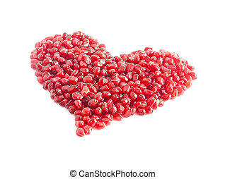 ripe pomegranate seeds in form of heart isolated on white...