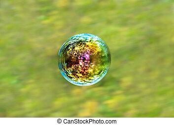 iridescent soap bubble on green forest background