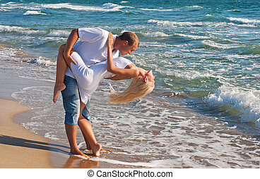 loving couple dancing on the sea beach at summer against sea...