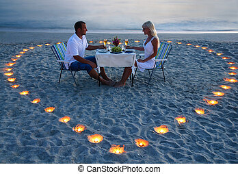A young lovers couple share a romantic dinner with candles...