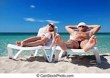 Young couple sunbathe on the beach bed on the sea beach