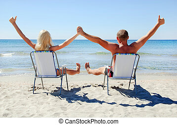 Positive young couple sitting on the beach chair on the sea...