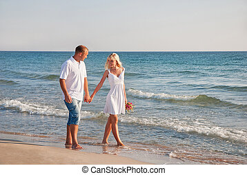 loving couple walking on the sea beach at summer with the bouque
