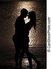 Young couple hug silhouette on a sea beach against sunset...