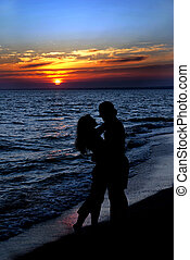 couple silhouette on beach against sunset - Young couple...