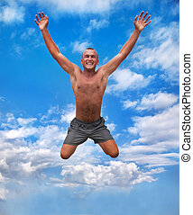 young man jumping in the air against a blue sky