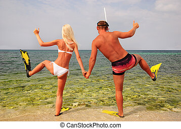 man and woman go to diving on summer beach - positive...