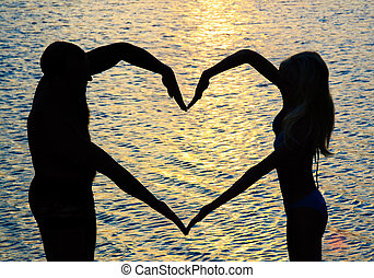 young couple making heart shape with arms on beach against...