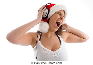 woman wearing christmas hat and enjoying music with white...