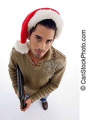 young man wearing christmas hat and holding laptop