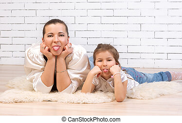 Mother and 5 year old daughter Tongue lying on the floor