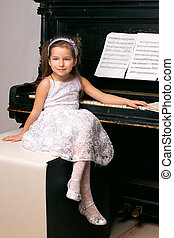 girl in a black dress sitting near the piano - 5 year old...