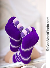 Female legs in purple socks with individual toes