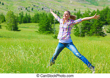 Happy girl jumping on the field