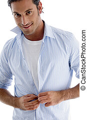 man tucking his shirt buttons against white background