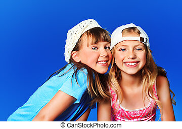 sisters - Two cheerful girls outdoor over blue sky.