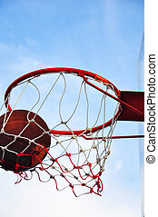 Picture of a basketball field goal with the sky in background