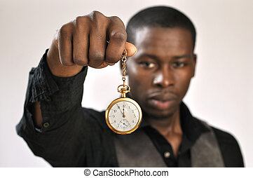 Time is ticking - Young man holds gold pocket watch showing...