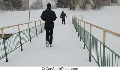 people snowstorm bridge
