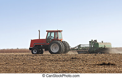 Farm Tractor - Farm tractor discing a field after harvest