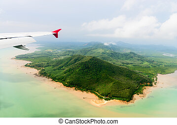 Aerial view of the tropical shore under airplane