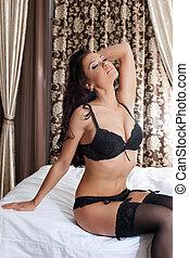 Hot brunette posing sitting on bed