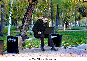 Man With Laptop Outdoor - Young man with Laptop sitting on...