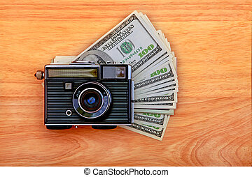 Vintage Camera And Money on the Wooden Background