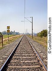 Railroad track through coutryside towards a cit - Vertical...