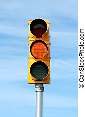 Yellow traffic signal light against blue sky