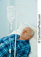 Patient at hospital with dropper - Adult patient lying on...