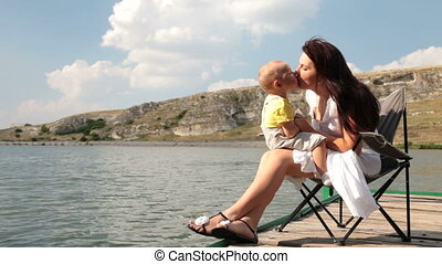 Mother with kid on nature - Mother and baby boy relaxing on...