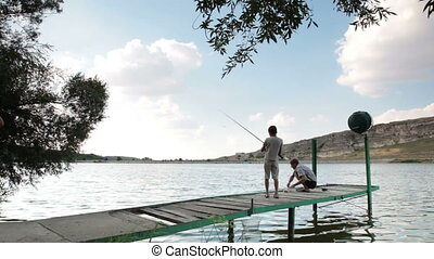 Father and son fishing by the lake