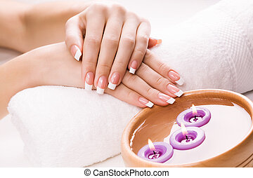 woman's hands with aromatic candles and towel. Spa - female...
