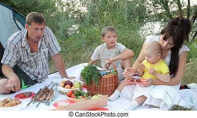 Young family camping - young family with two children having...