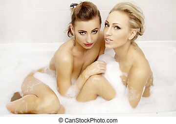 Two attractive woman in bath relaxing. - Two attractive...