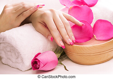 beautiful manicure with fragrant rose petals and towel Spa -...